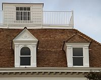 The roof of a house with a widow's walk on top, consisting of a small room surrounded by railing