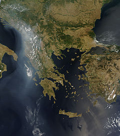 A satellite view of the Balkans and Greece. Clouds and smoke trails are seen above the Balkans and trailing south into the Ionian Sea.