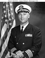 Top half of man in circa 1970 U.S. Navy officer uniform, before an American flag.