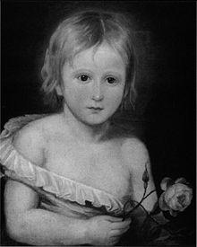 Portrait en noir et blanc, montrant en buste un tout jeune enfant, portant une petite chemise qui tombe de son corps, révélant la moitié de sa poitrine. Il a une courte cheveleure blonde et tient une rose.