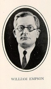 Formal portrait of William Empson, wearing eyeglasses and dressed in a coat and tie