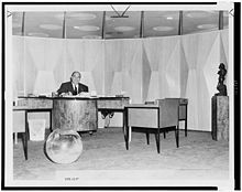A man in a suit sits behind a desk in an office decorated with cube chairs and a glass sphere.