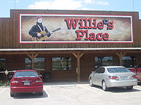 "A store with a sign that reads ""Willie&squot;s Place"". The apostrophe is replaced in the sign by a bullet hole. The structure of the store is constructed in wooden with three columns. There are four windows and there are a red and a grey car in the parking lot."