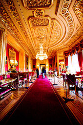 A photograph of a large room with a long red carpet stretching through the middle of it and windows on the right hand side. Furniture fills both sides of the room. The ceiling contains ornate plasterwork and a chandelier hangs down from the middle of the picture.