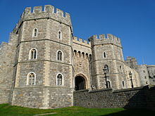 A photograph of a stone gatehouse, with angular octagonal towers and windows picked out in white stone. The weather is good, with the sky behind the gatehouse a bright blue.