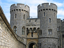 A photograph of a stone gatehouse, with two large, circular towers on each side of the gateway dominating the picture. A stone wall stretches alongside the left hand side of the picture.