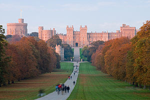 A red coloured castle with battlements and towers lies in the distance of the photograph. A path curves from the bottom of the picture towards it, with various people strolling along it. On either side is flat grass and green woodlands.