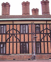 A close-up photograph of a building made with black timbers and red brick. The building has four tall, brick chimneys. A relatively modern drainpipe comes down the middle of the building.