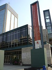 The Francis Winspear Centre for Music with a banner in front for the Edmonton Symphony Orchestra and Century Place tower behind it.