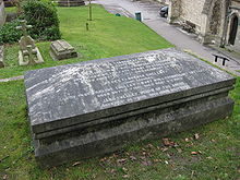 Photographie d'une tombe de granit en forme de cercueil.