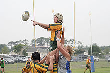 A female player in yellow and green kit and wearing a white scrum cap, jumps to collect a ball while supported by team mates.