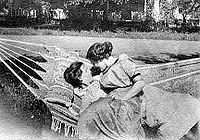 Black and white photo of two women sitting in a hammock in turn of the 20th century dresses; one reclines and the other sits on her lap and wraps her arm around the other, both staring at each other