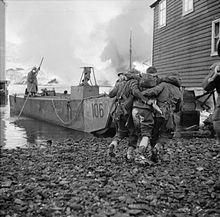 two men each side of a wounded man, helping him towards a boat docked between houses