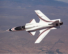 Top aerial view of white jet aircraft banking left in-flight. It shows the aircraft's forward swept wings, and trapezoidal canards located just aft of the canopy