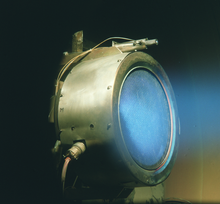 A metal cylinder with electrodes attached to its side. Blue diffuse light is coming out of the tube.