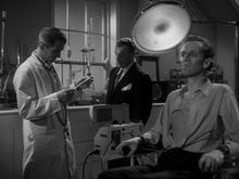 A black-and-white screenshot from the film depicting a tall man in a white coat reading a clipboard watched by a man with a moustache wearing a dark suit. In the foreground a man is seated rigidly staring straight ahead, his eyes and face sunken into a skeletal appearance