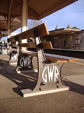 """A bench seen from low down and behind. Three brown-painted cast iron legs have """"G W R"""" cast into them in a circular mofif and painted white, and support two pairs of widely spaced wooden planks that form the seat and back."""