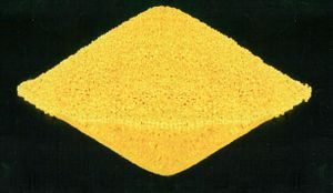 A yellow sand-like rhombic mass on black background.