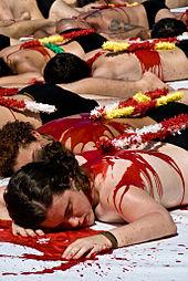 photo couleur montrant un groupe de personnes dénudées étendues sur le sol et simulant la mort, avec du sang et des banderilles sur le dos