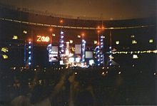 """An elaborate concert stage set bearing a logo that reads """"Zoo TV"""", set in a dark stadium. Towers reach into the night sky, illuminated in blue with red warning lights on top."""