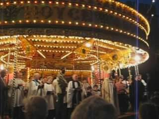 Church choir sing at fair. A merry-go-round fills most of the background.