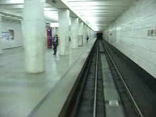 A silent video shot from the perspective of the driver's cab of a metro train. It travels in a dark tunnel and then stops at the underground station, which is lit up in white and supported by the pillar-trispan structure.