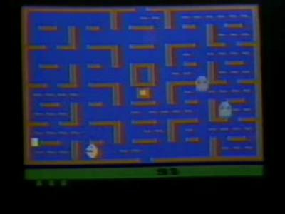 A video depicting the game's method of play. The main character travels through the corridors of a brown maze to eat white wafers, while avoiding four flickering ghosts.