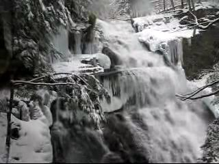 A video taken in winter from the trail starts by looking up to the head of the waterfalls and then pans slowly down and to the right to follow the falling water cascading down a stone face. The thundering water flows freely, but the surrounding rocks and trees are covered in snow and ice.