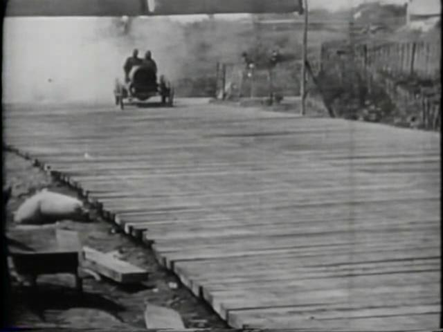 A car drives off a wooden plank road, before reversing back onto the track and continuing